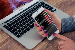 Planowanie mediów. kobieta przegląda dane na smartfonie, w tle laptop