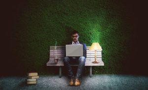 Dla psychologów pracoholizm nie jest zasługą, a zaburzeniem. Mężczyzna pracujący po godzinach przy lampce.