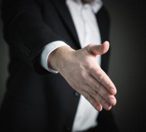 wyciągnięta przed siebie ręka na powitanie podczas rozmowy rekrutacyjnej